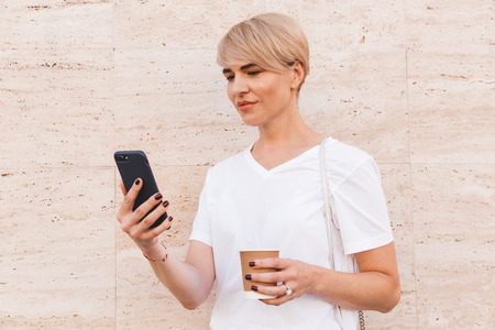 Image closeup of caucasian blond woman wearing white t-shirt using cell phone while standing against beige wall outdoor in summer and drinking coffee from paper cup