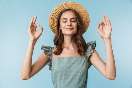 Close up portrait of a calm woman in dress and summer hat showing ok gesture isolated over blue background