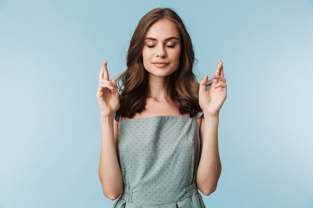 Portrait of a calm young woman in dress holding fingers crossed for good luck isolated over blue background Foto de archivo