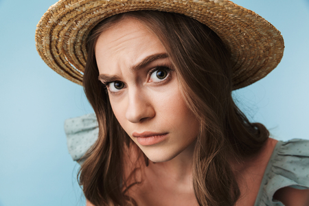 Close up portrait of a curious woman in dress and summer hat looking closely at camera isolated over blue background Stock Photo