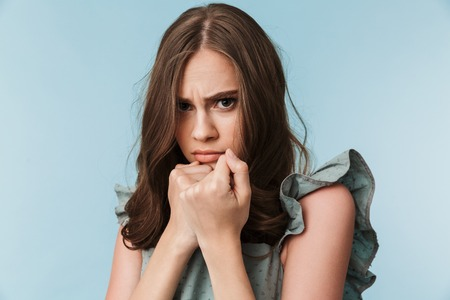 Close up portrait of a scared young woman in dress looking at camera isolated over blue background