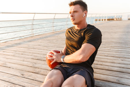 Concentrated young sportsman in earphones doing exercises with a heavy ball at the seaside