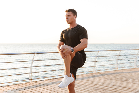 Concentrated young sportsman in earphones doing stretching exercises at the seaside