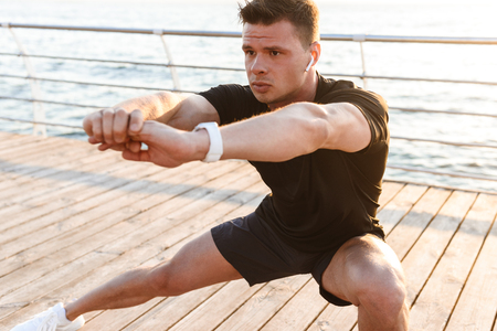 Focused young sportsman doing lunges at the seaside