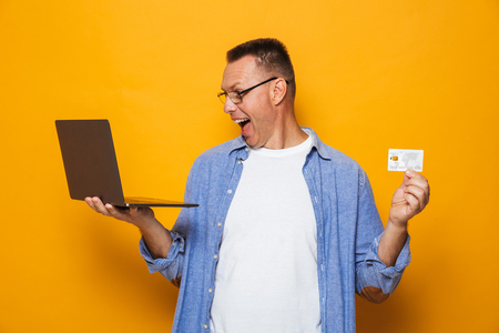Image of screaming excited man isolated over yellow background using laptop computer holding credit card.