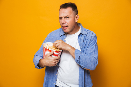 Photo of emotional concentrated man isolated over yellow background eating pop corn watch film looking camera.