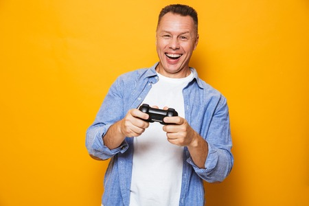 Photo of emotional man isolated over yellow background play games with joystick.