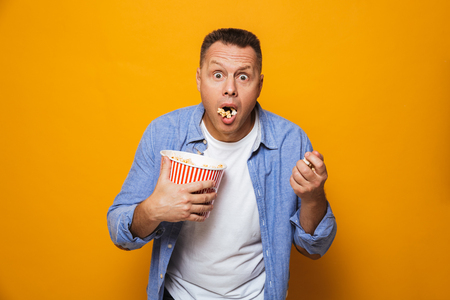 Image of shocked man isolated over yellow background eating pop corn watch film looking camera.