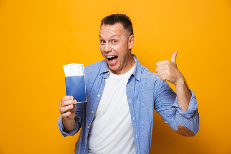 Photo of excited happy man isolated over yellow background holding passport showing thumbs up. Stok Fotoğraf