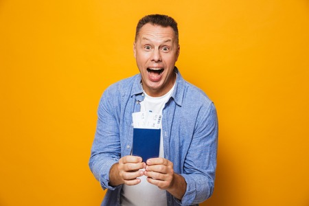 Photo of excited happy man isolated over yellow background holding passport. Stok Fotoğraf