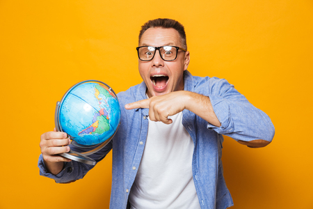 Photo of emotional man isolated over yellow background holding globe pointing.