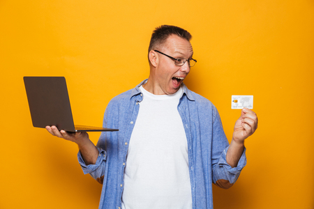 Image of screaming excited man isolated over yellow background using laptop computer holding credit card. Stok Fotoğraf - 107166933