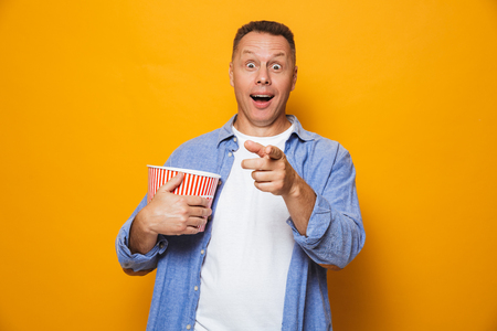 Photo of emotional excited man isolated over yellow background eating pop corn watch film looking camera. Stock Photo