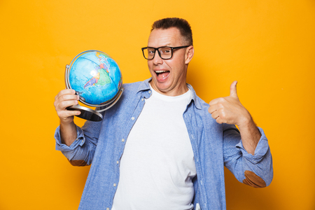 Photo of emotional man isolated over yellow background holding globe make thumbs up gesture.