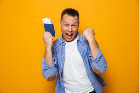 Photo of excited happy man isolated over yellow background holding passport make winner gesture. Stok Fotoğraf