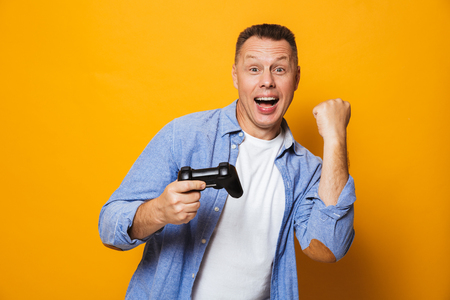 Photo of emotional man isolated over yellow background play games with joystick make winner gesture.