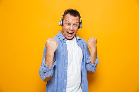 Image of excited emotional man isolated over yellow background listening music with headphones make winner gesture.