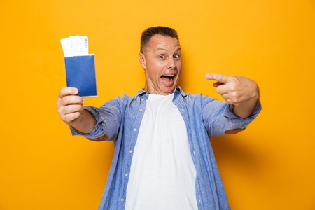 Photo of excited happy man isolated over yellow background holding passport pointing. Stok Fotoğraf