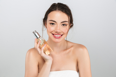 Beauty portrait of a smiling young woman with make-up holding an oil bottle isolated over gray background