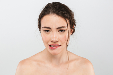 Beauty portrait of a seductive young woman with make-up looking at camera isolated over gray background
