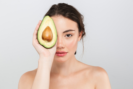 Beauty portrait of a lovely young topless woman with make-up holding sliced avocado isolated over gray background Foto de archivo