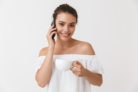 Portrait of a smiling young casual brunette woman talking on mobile phone holding cup of coffee isolated over white background