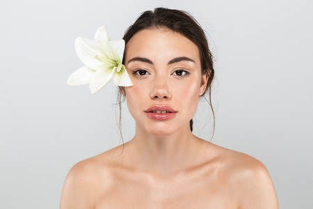 Beauty portrait of a pretty young topless woman with make-up posing with lily flower at her face isolated over gray background