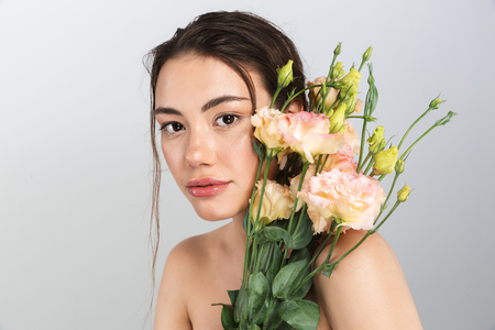 Beauty portrait of a lovely young topless woman with make-up posing with eustoma flowers bouquet at her face isolated over gray background Stockfoto