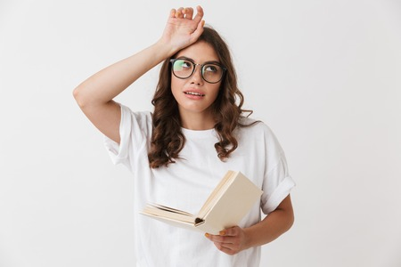 Portrait of a tired young casual brunette woman in eyeglasses holding paper book isolated over white background Imagens