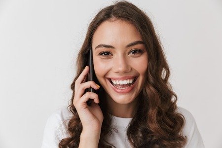 Close up portrait of a laughing young casual brunette woman talking on mobile phone isolated over white background