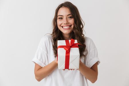 Portrait d'une jeune femme brune décontractée excitée tenant présent fort isolé sur fond blanc