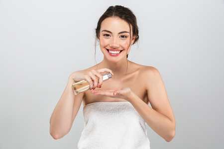 Beauty portrait of a cheerful young woman with make-up applying oil from a bottle isolated over gray background Imagens