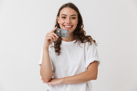 Portrait of a smiling young casual brunette woman holding credit card isolated over white background Foto de archivo
