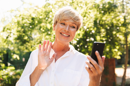 Happy mature woman having a video chat through mobile phone while resting at the park Stockfoto