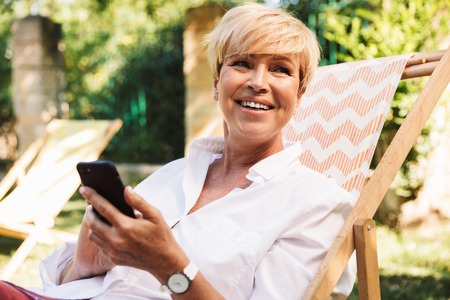 Happy mature woman using mobile phone while resting at the park