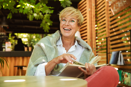 Happy mature woman wrapped in blanket reading a book while sitting at a cafe Foto de archivo