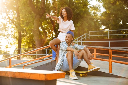 Portrait of a cheerful young african couple with skateboards sitting together at the skate park showing thumbs up Imagens