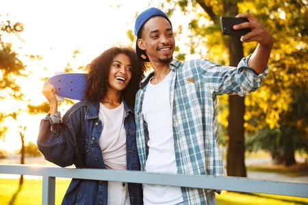 Retrato de una joven pareja africana feliz con patinetas tomando un selfie juntos en el parque de patinaje
