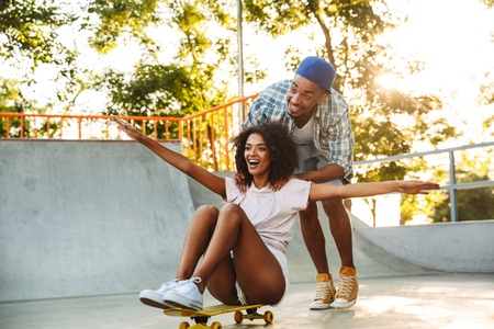 Portrait of a happy young african couple with skateboards having fun together at the skate park