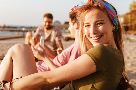 Picture of friends have a rest outdoors on the beach drinking beer. Focus on blonde woman looking camera.