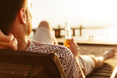 Picture of handsome man have a rest outdoors on the beach drinking beer.