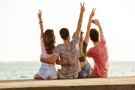 Picture of group of four friends loving couples walking outdoors on the beach showing peace gesture make a selfie.