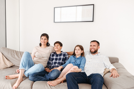 Image of caucasian family with two children resting in living room at home and looking at tv together while sitting on sofa