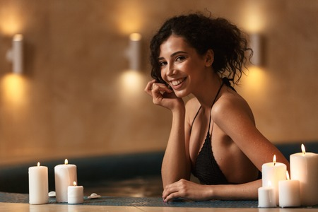 Image of young cheerful happy beautiful woman in spa lies resting with candles. 版權商用圖片
