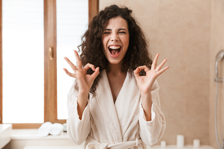 Image of excited beautiful young cute woman looking camera in bathroom showing okay gesture.