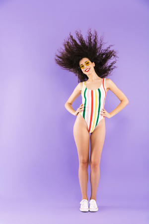 Full length photo of trendy attractive woman in swimsuit and sunglasses fooling around with shaking hair isolated over violet background in studio