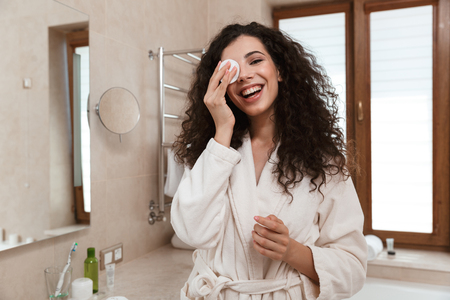 Photo of young pretty woman in bathroom take care of her skin.