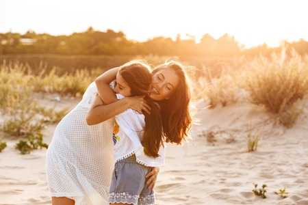 Photo of young cute happy family having fun together outdoors at the beach. Stock Photo