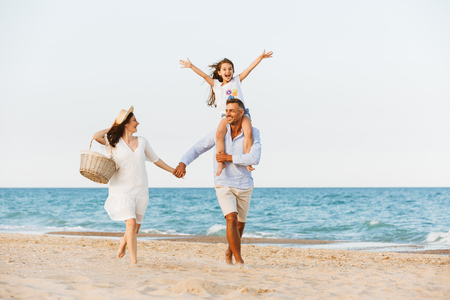 Photo of young cute happy family having fun together at the beach. Stock Photo