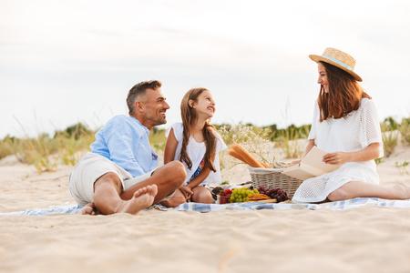 Familia riendo con padre, madre, hija haciendo un picnic en la playa Foto de archivo
